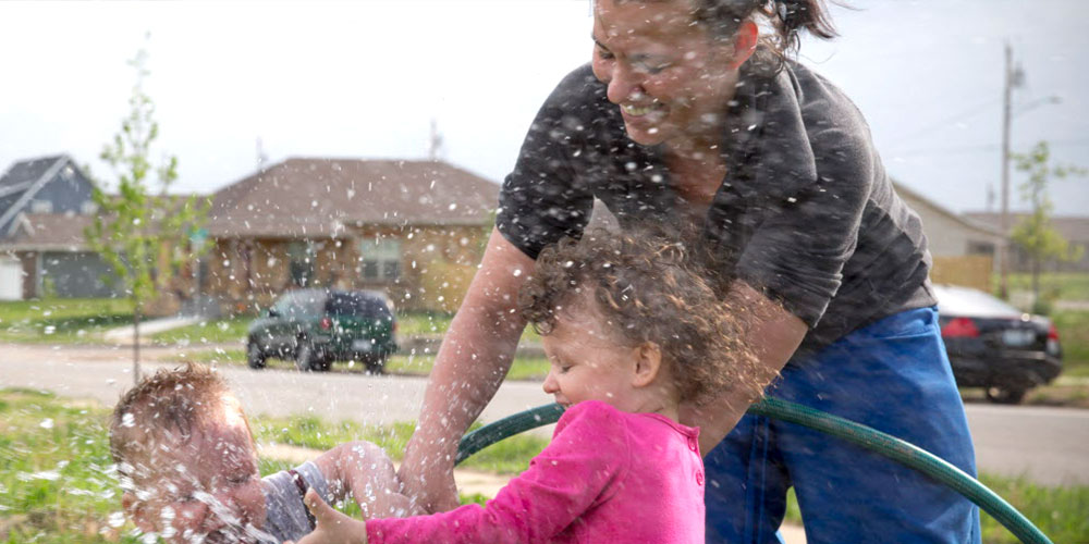 family playing with hose